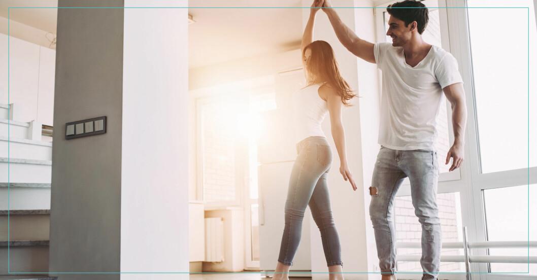 Ung kvinna och man dansar i ljust rum.