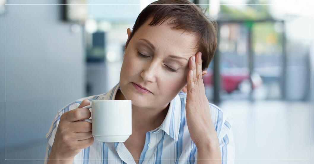 Kvinna med huvudvärk som dricker kaffe.