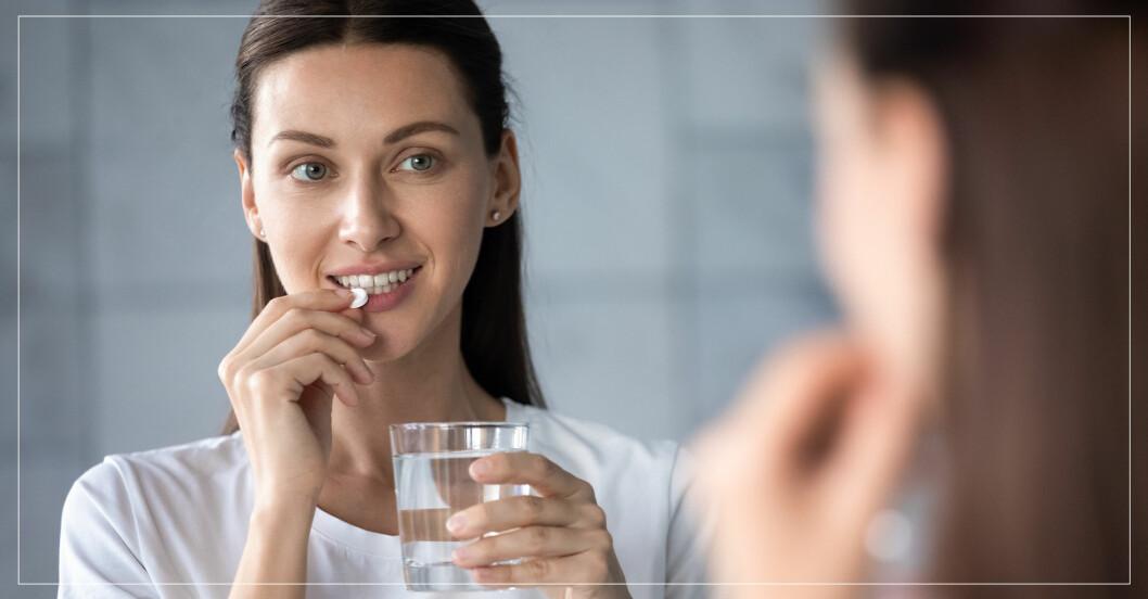 Kvinna som tar ett kosttillskott för hår, hud, och naglar tillsammans med ett glas vatten.