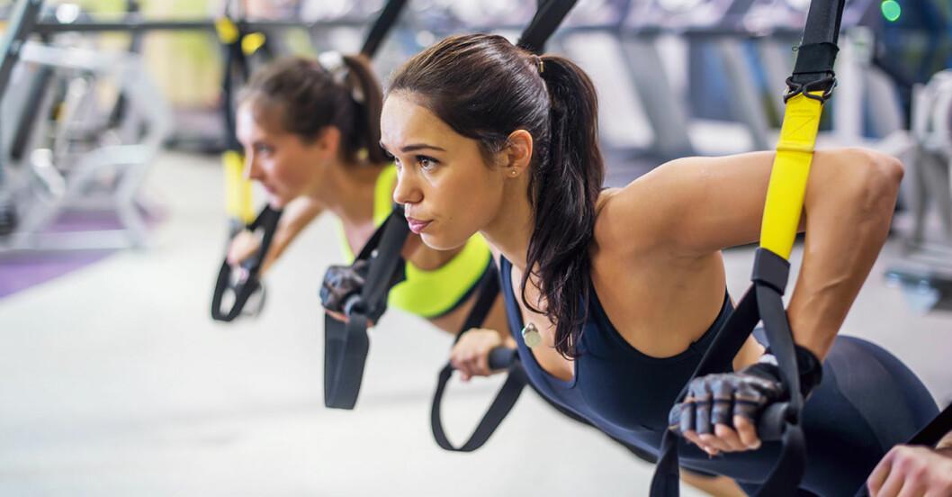 Två kvinnor styrketränar med trx-band