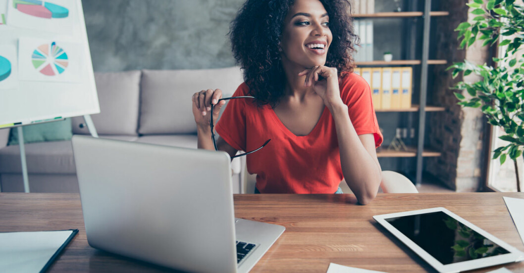 Glad kvinna sitter på jobbet