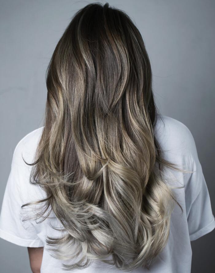 Kvinna med långt vågigt hår i askiga nyanser.