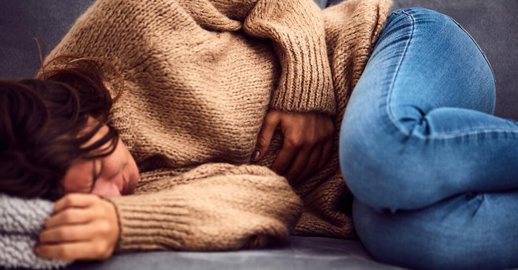 Kvinna ligger i soffan med ont i magen misstänkt missfall