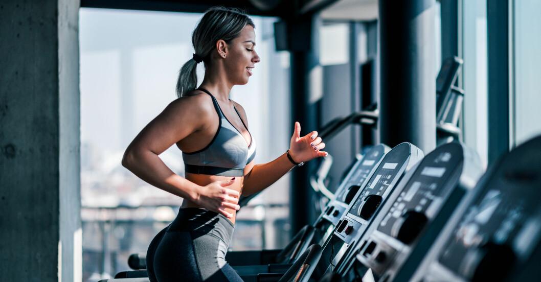 Kvinna på löpband i corona-anpassat gym