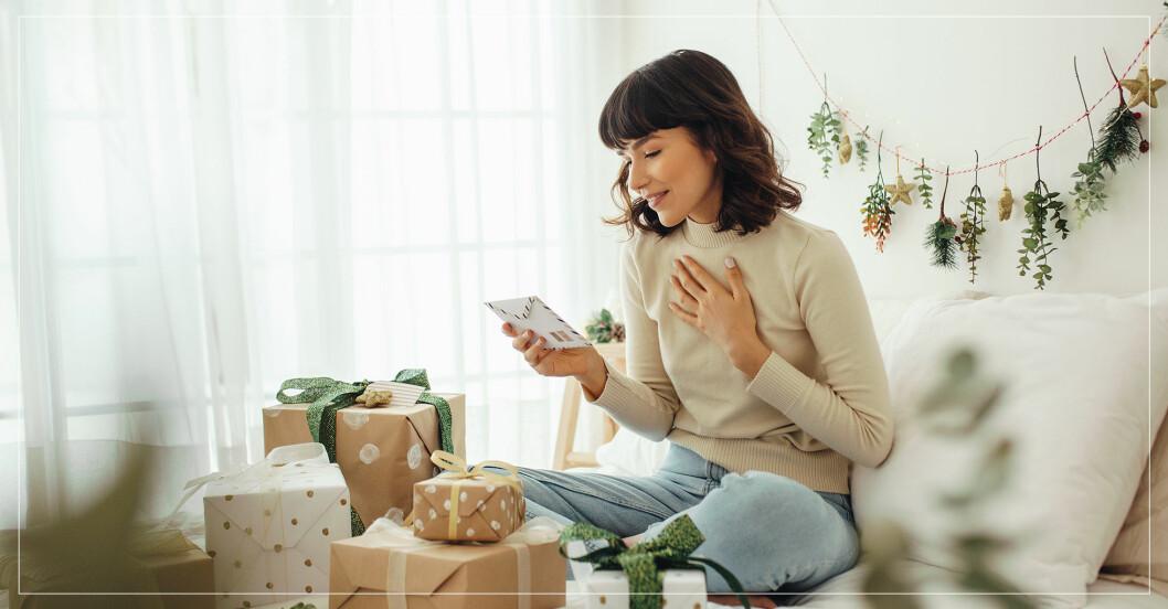 Kvinna sitter i sängen med en många paket och läser ett julkort.