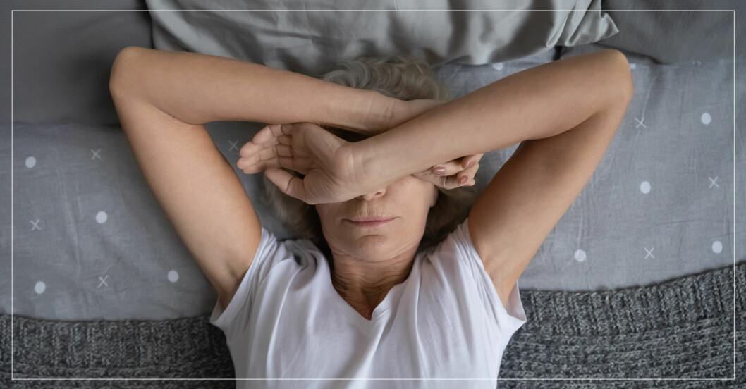 Kvinna som inte kan sova i grå säng.