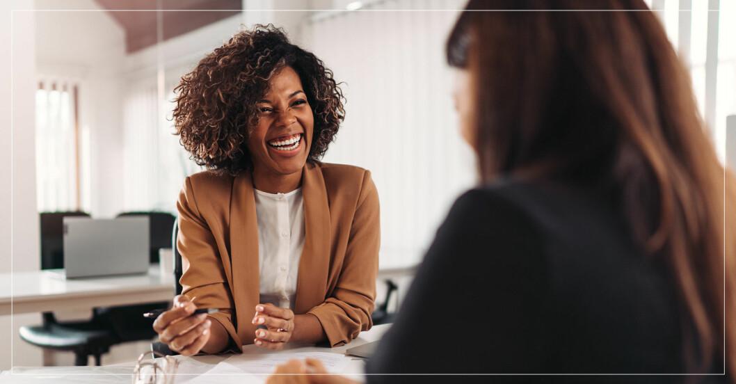 kvinna som ler mot kollega på jobbet