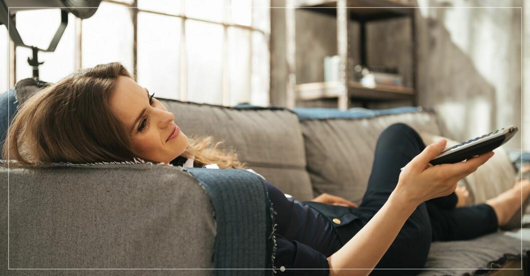 Kvinna tar det lugnt på soffan medan kroppen förbränner kalorier.