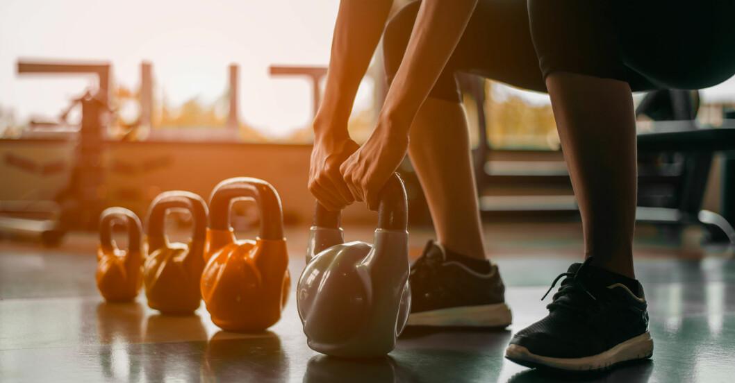 Kvinna tränar med kettlebells-vikter