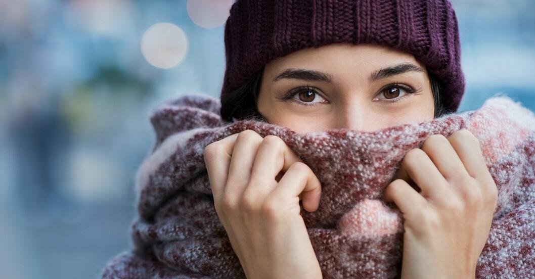 Kvinna i mössa och halsduk som fryser