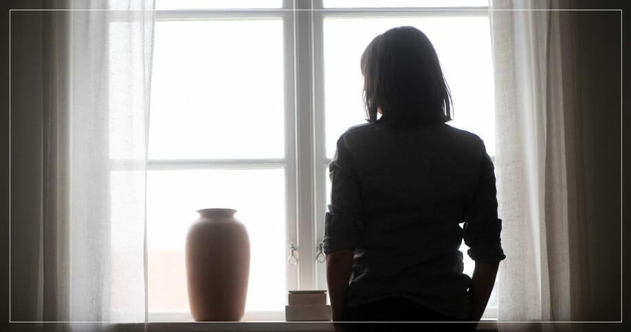 Kvinna tittar ut genom fönstret från ett mörkt rum
