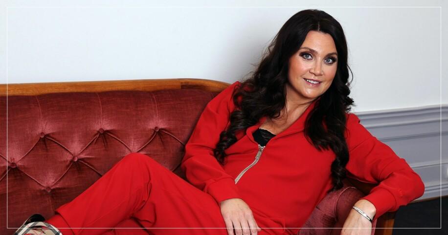 Camilla Läckberg sitter i en soffa
