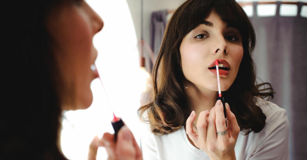Kvinna har läppglans på sina läppar.