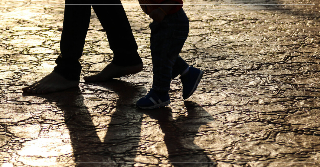 pappa och barn som går tillsammans, fötterna som skuggar marken.