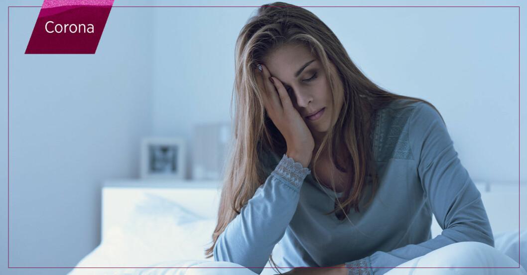 Utmattad kvinna sitter i sin säng