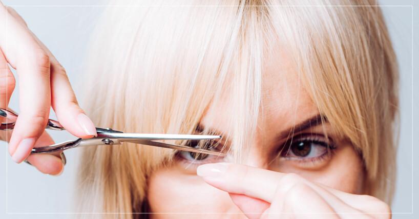 person med blondt hår håller i en sax och är på väg att klippa i sin lugg
