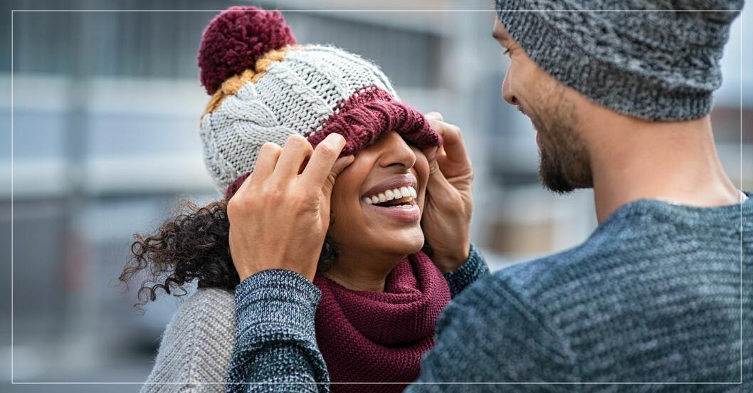 skrattande par där mannen drar ner kvinnans mössa
