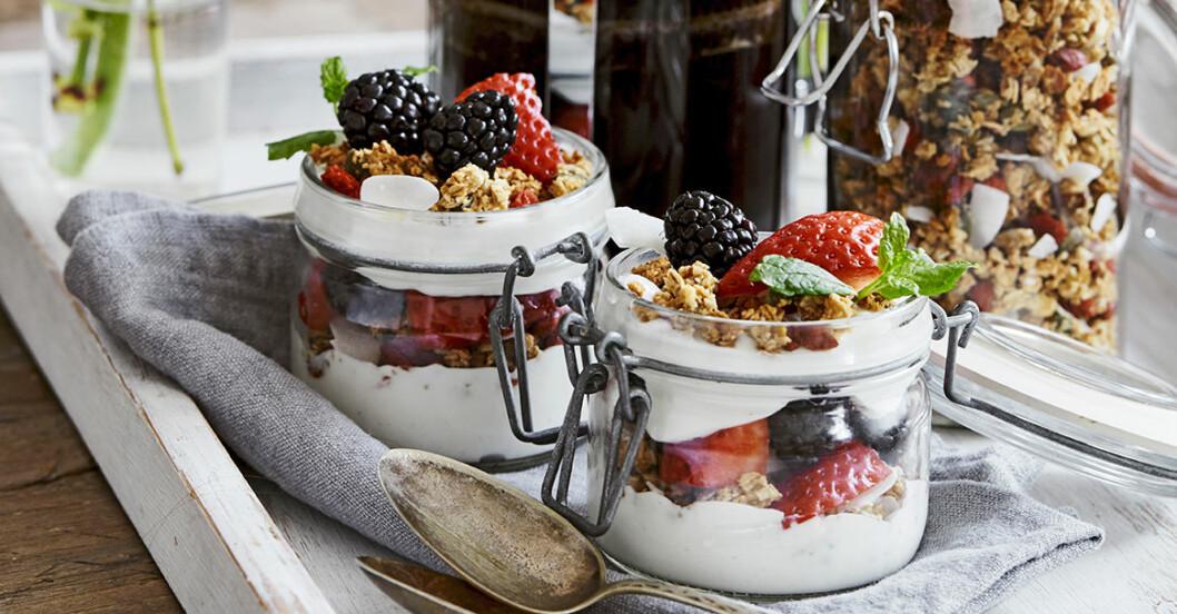 Två glasburkar med yoghurt, jordgubbar, björnbär och granola på fin dukning