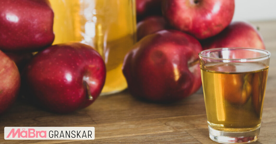 Äpplen och ett glas med äppelcidervinäger