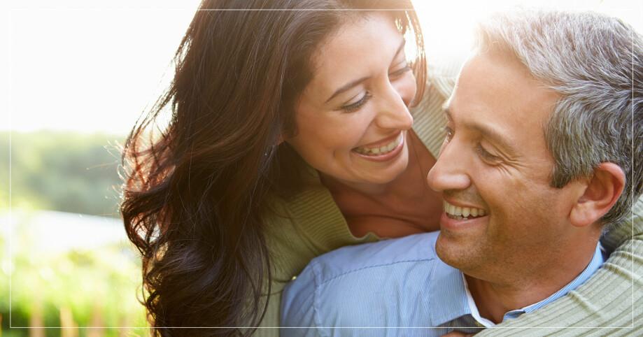 En kvinna och en man som tittar på varandra och ler.