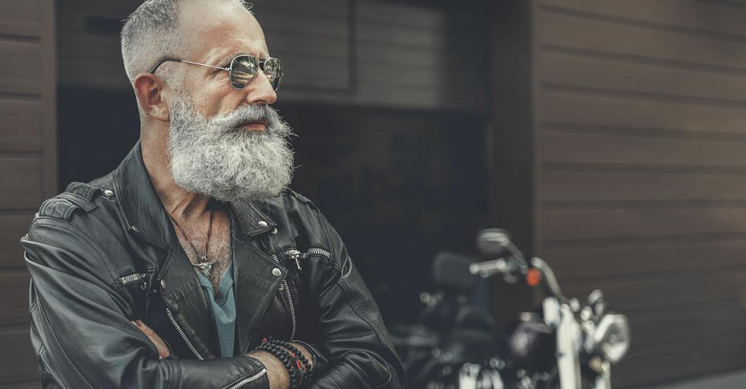Äldre man med grått skägg och armarna i kors står framför en garageport och en motorcykel.
