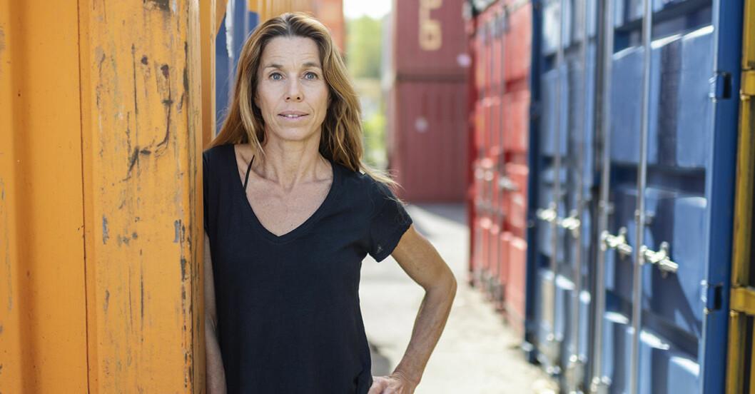 Magdalena Forsberg står bland containrar och ser allvarlig ut
