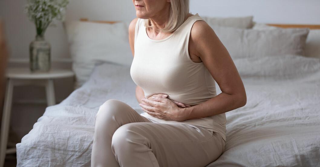 Kvinna med magknip sitter i sängen och håller sig om magen