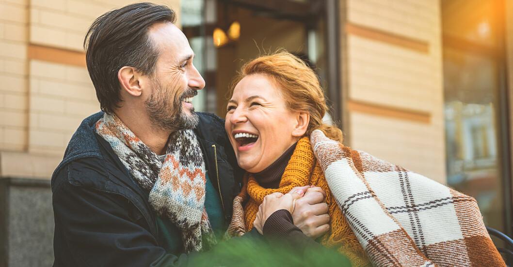 Skäggig man håller armen runt rödhårig kvinna med filt över axlarna som skrattar
