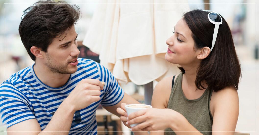 Ung man och kvinna med kaffekopp i handen sitter utomhus och pratar.