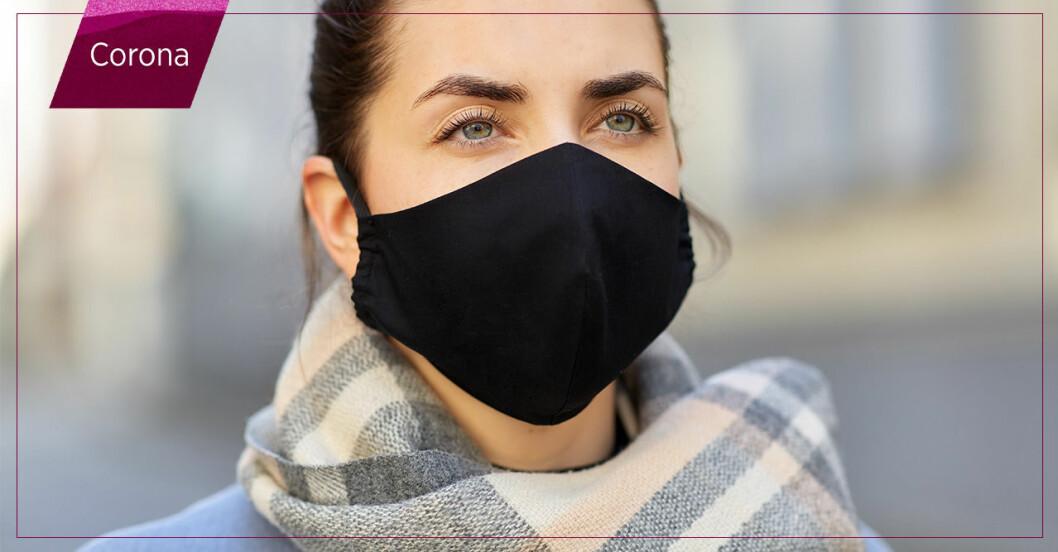 kvinna med svart munskydd i tyg