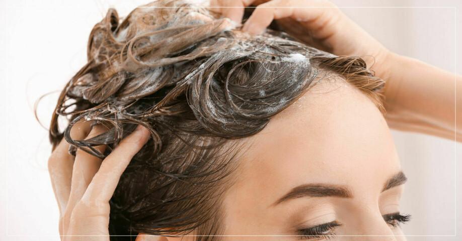 Kvinna masserar hårbotten i duschen