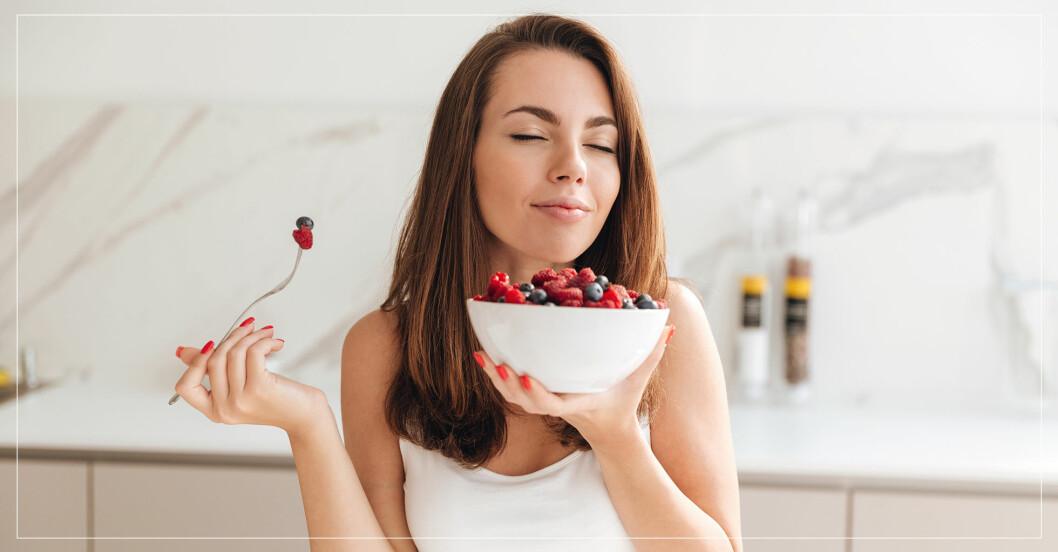Kvinna som äter njuter av en skål med bär i lugn och ro.