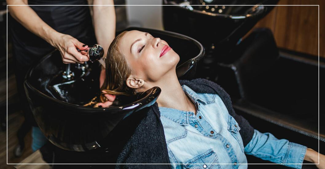 kvinna som tvättar hår hos frisör