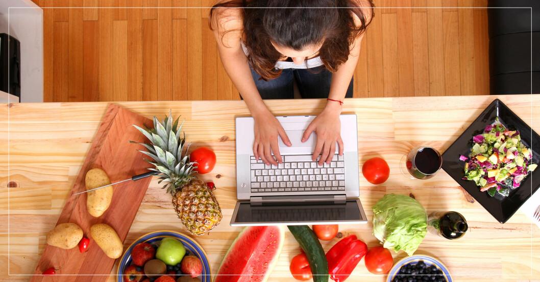 kvinna som lagar mat och sitter med sin laptop