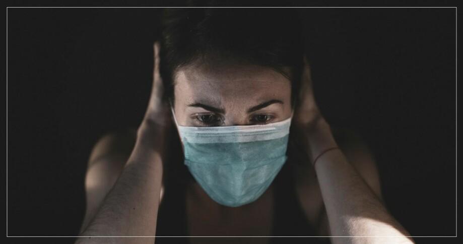 Kvinna med munskydd som håller sig för huvudet
