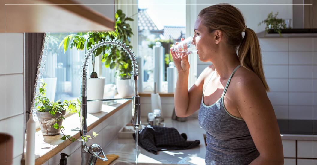 Kvinna som dricker vatten i köket