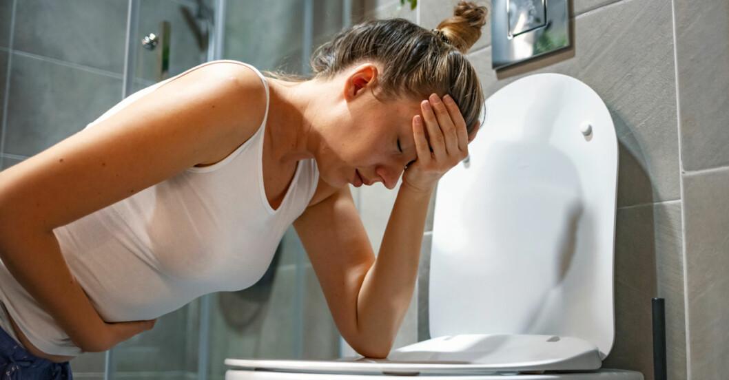 Illamående kvinna hukar över toastolen för att kräkas