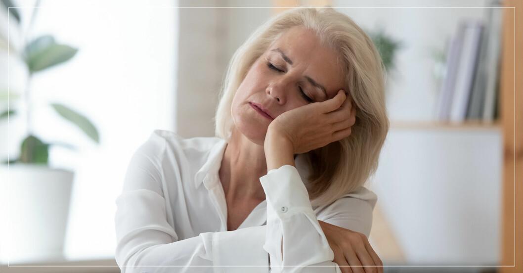 trött kvinna lutar huvudet i sin hand