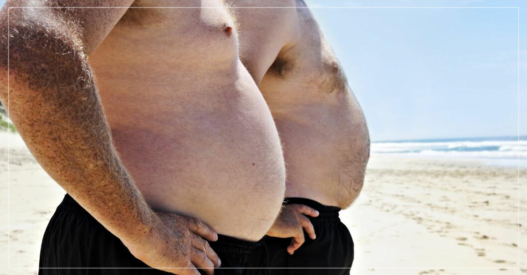 Två män med ölmage på en strand