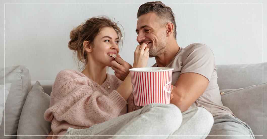 Par äter popcorn i soffan.