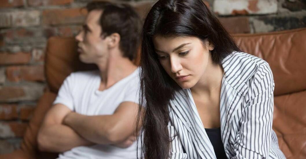 Par som har grälat sitter i en soffa