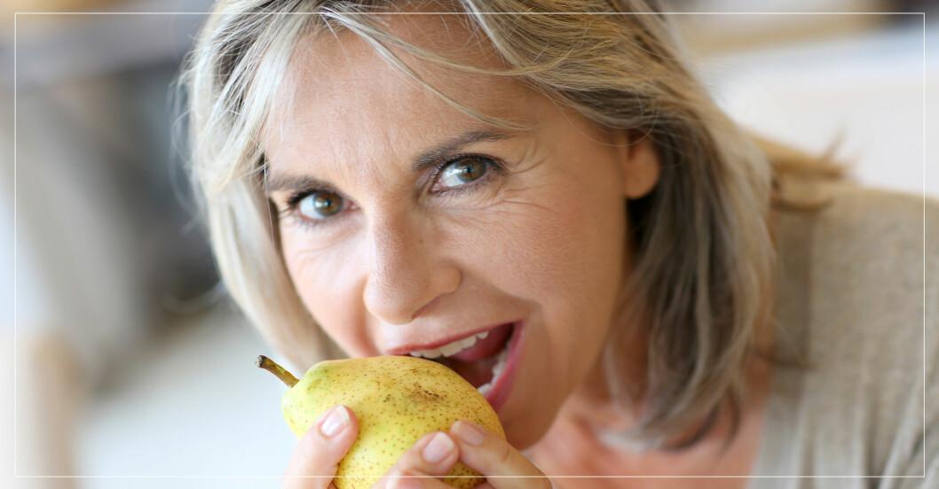 Äldre kvinna tar en tugga på ett päron