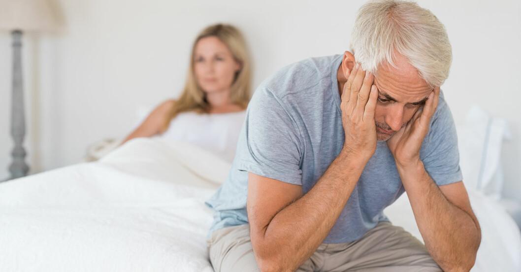 Vithårig man sitter på sängkanten med huvudet i händerna i bakgrunden ligger kvinna