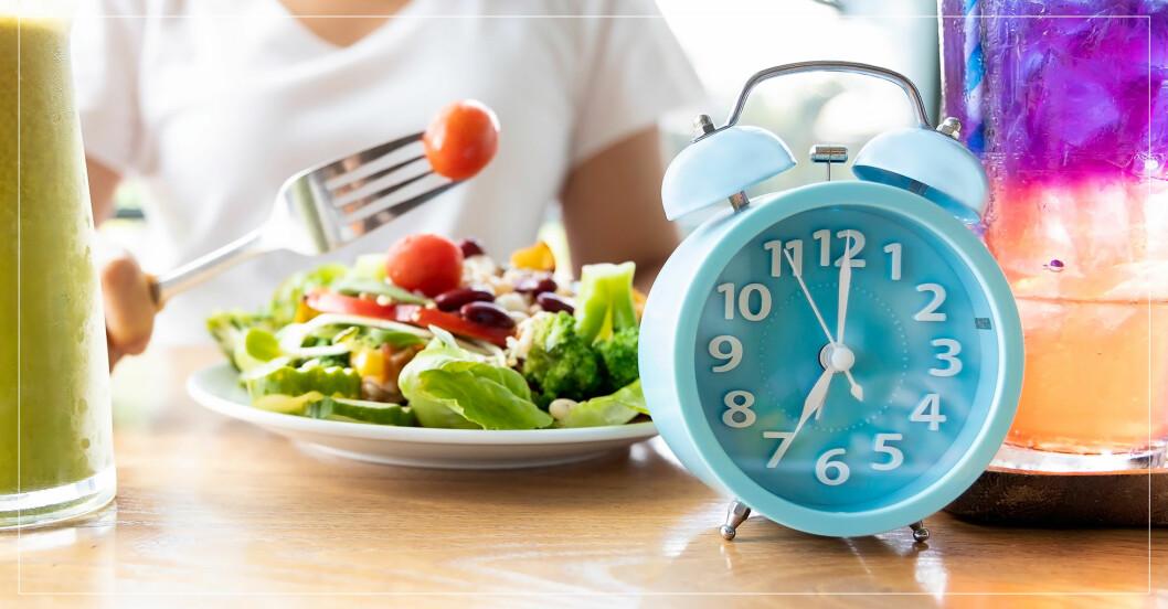 En klocka och en tallrik mat som illustrerar periodisk fasta.