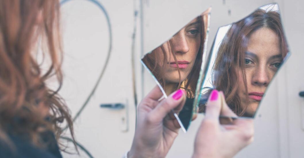 kvinna som haft sönder spegel och tittar i skärvorna