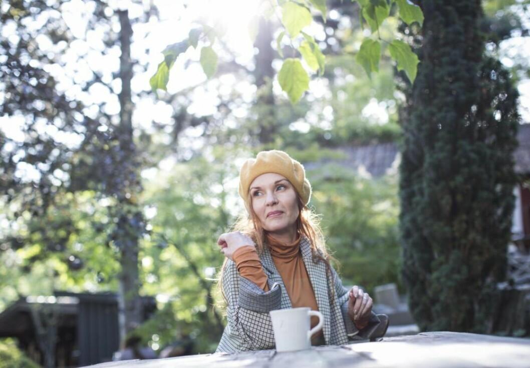 Pia Johansson sittter utomhus med en kaffemugg framför sig.