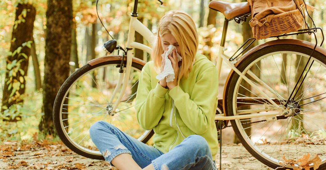 Kvinna sitter ner i naturen och snyter ut pollen ur näsan
