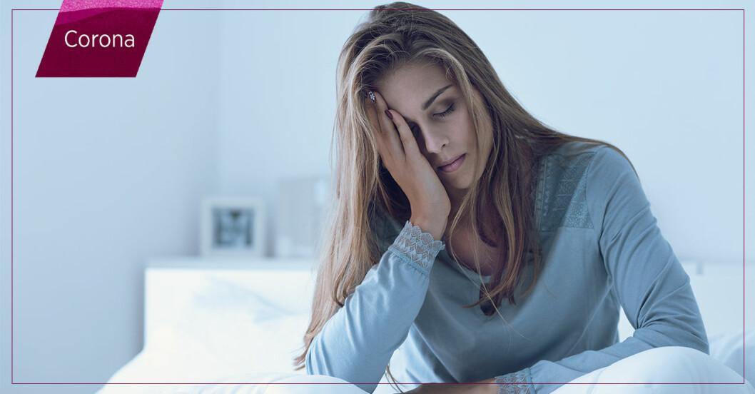 Extremt trött kvinna som sitter i sängen med postcovid.