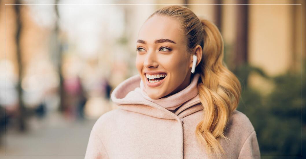 Kvinna som ser glad ut och har hörlurar i öronen.