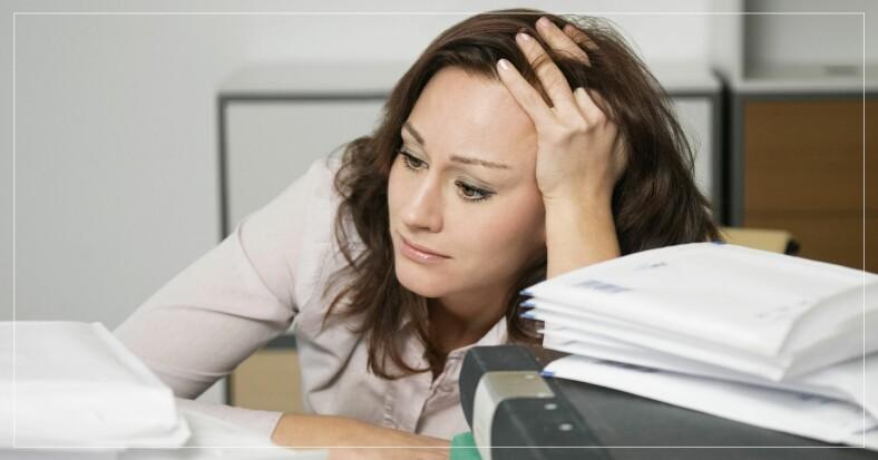 Förtvivlad kvinna med pärmar och dokument framför sig